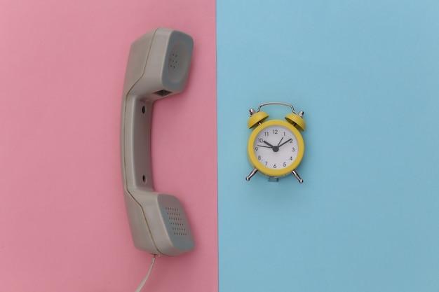 Receptor de teléfono retro y reloj despertador sobre fondo rosa pastel azul.