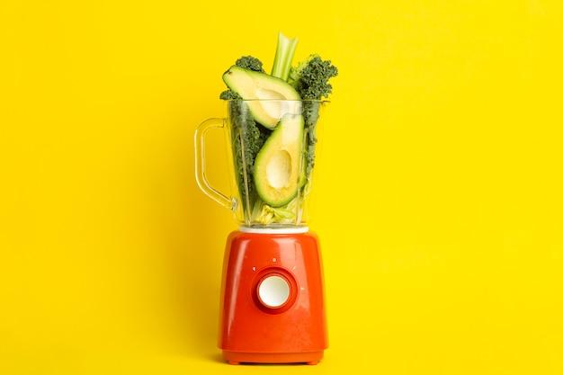 Receta de batido. batido verde de verduras (aguacate, apio, ensalada cale, espinacas) en una licuadora sobre un fondo amarillo. concepto de desintoxicación de comida vegana y saludable