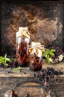 Receta casera de jarabe de saúco negro en una botella de vidrio sobre una mesa de madera. bayas frescas en el fondo. copia espacio