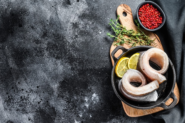 Receta para cocinar filete de merluza en una sartén. fondo negro. vista superior. copie el espacio.