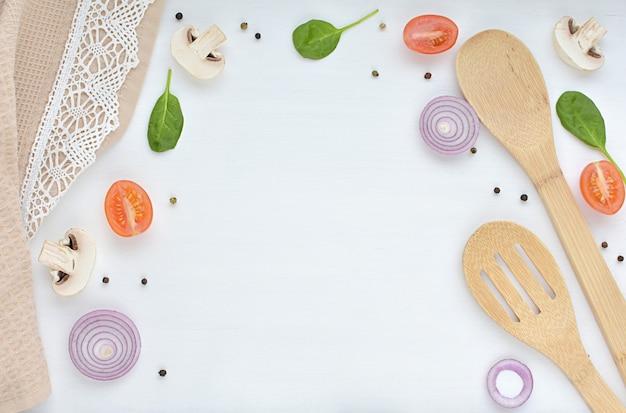 Receta, concepto de cocina, cucharas de madera, manteles con cordones, vegetales y especias.