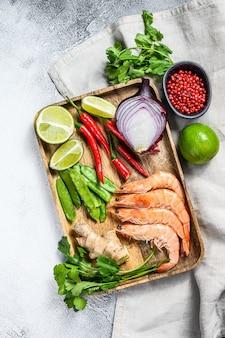 Receta e ingredientes tom kha gai. sopa de pollo galangal tailandés en leche de coco. vista superior