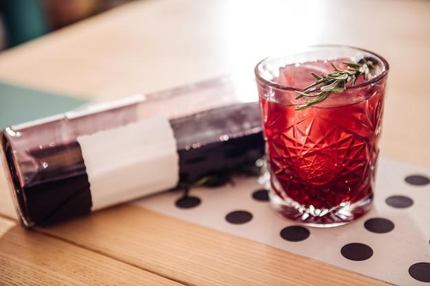 Receta especial. cóctel alcohólico frío de pie cerca de la botella mientras se sirve