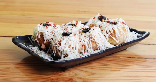 Receta de fusión de pani puri indio a pizza italiana en mesa de madera