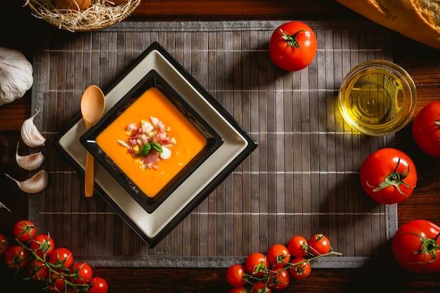 Receta típica española de salmorejo cordobés en un plato cuadrado con algunos ingredientes alrededor sobre una mesa de madera.