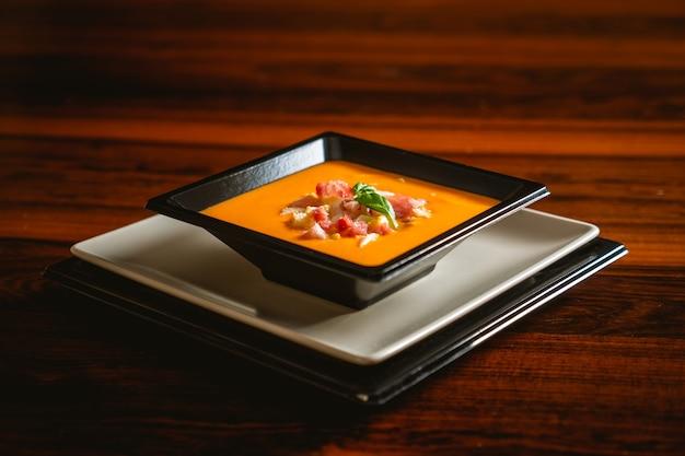 Receta típica española de salmorejo cordobés en un plato cuadrado sobre una mesa de madera