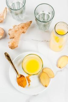 Recetas de cocina india. alimentos saludables desintoxicación de agua. bebida refrescante india tradicional de cúrcuma y jengibre en botellas de vidrio sobre una mesa de mármol blanco.