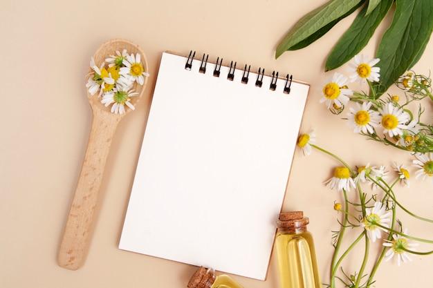 Recetas concepto de belleza. cuaderno, botellas de esencia, margaritas planas con espacio de copia