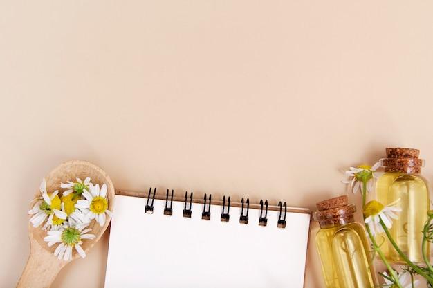 Recetas concepto de belleza natural. cuaderno, botellas de esencia, pétalos, margaritas planas con espacio de copia