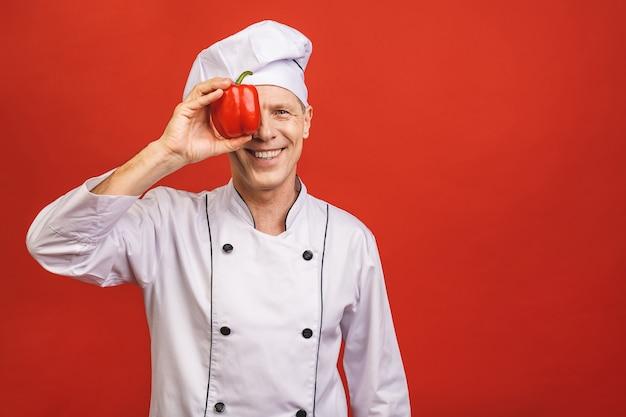 Recetas de verduras. cocinero sonriente man holding red sweet pepper que cocina la comida que se coloca sobre fondo rojo aislado del estudio.