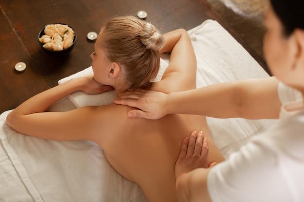Recibir un masaje. mujer tranquila con cuerpo en forma acostada en una cama cubierta en gabinete equipado y masajeando su espalda
