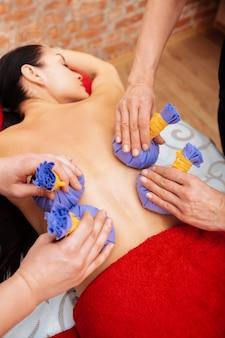 Recibir un tratamiento calmante. maestros profesionales en el salón de spa que brindan masajes con bolsas de hierbas a una hermosa cliente de cabello oscuro
