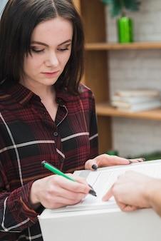 Recibo de firma de mujer joven para el paquete