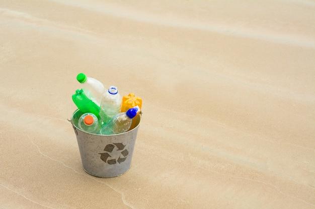 Reciclar, cesta con botella de plástico en la playa.
