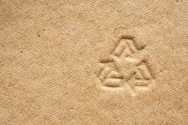 Reciclar signo en textura de papel cartón marrón
