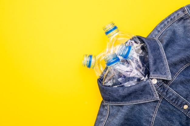 Reciclar la tecnología de botella de plástico para hacer ropa. vista superior vieja botella de agua y jeans de camisa azul