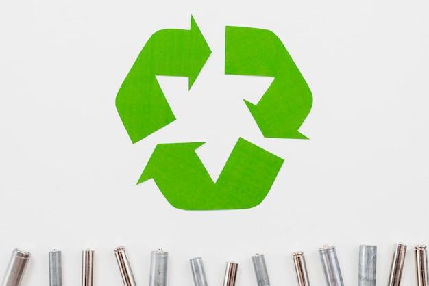 Recicle las pilas de símbolo y basura sobre fondo gris