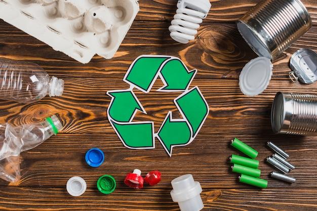 Recicle el símbolo rodeado con los artículos inútiles en el fondo texturizado de madera marrón