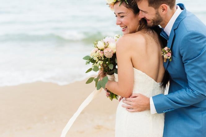 Recién casados alegres en ceremnoy de la boda de la playa