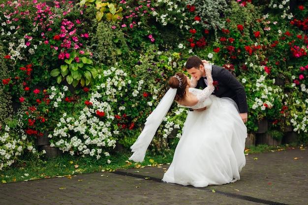 Los recién casados bailan en la naturaleza contra el fondo de un jardín de flores de color rosa