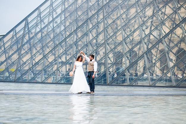 Recién casados bailando frente al museo del louvre