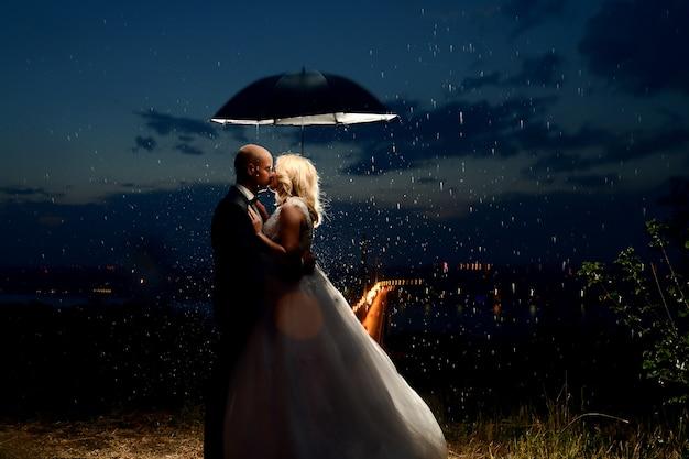 Recién casados besándose bajo la lluvia
