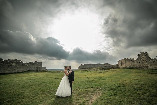 Recién casados besándose con ruinas de fondo