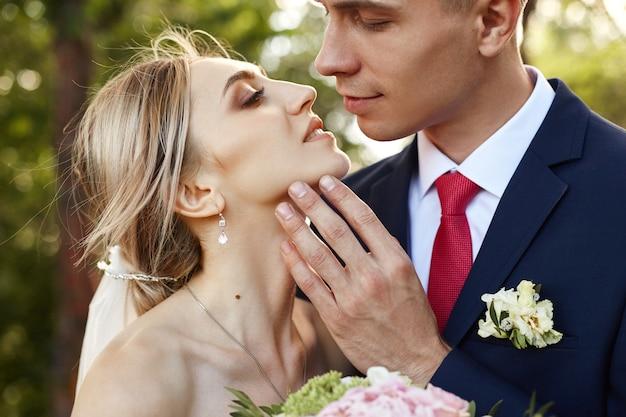 Recién casados caminan por la naturaleza en el parque después de la ceremonia de la boda