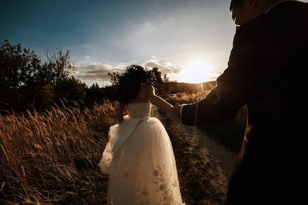 Recién casados caminando al atardecer en el campo