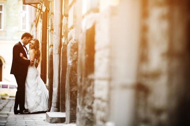 Recién casados enamorados posando en la calle