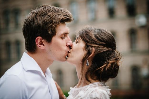 Los recién casados están de pie y besándose cerca del edificio antiguo afuera, palacio vintage al aire libre. ceremonia de la boda.