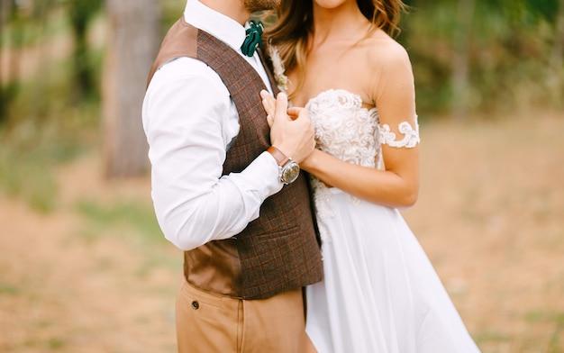 Recién casados con estilo posando abrazándose en la naturaleza verde