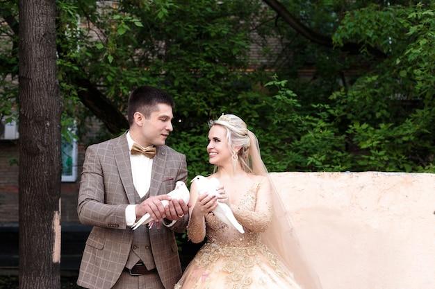 Unos recién casados felices y hermosos sostienen palomas. boda al aire libre.