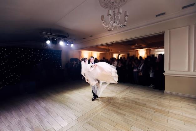 Los recién casados giran en la danza de la boda el novio sostiene a la novia en sus brazos
