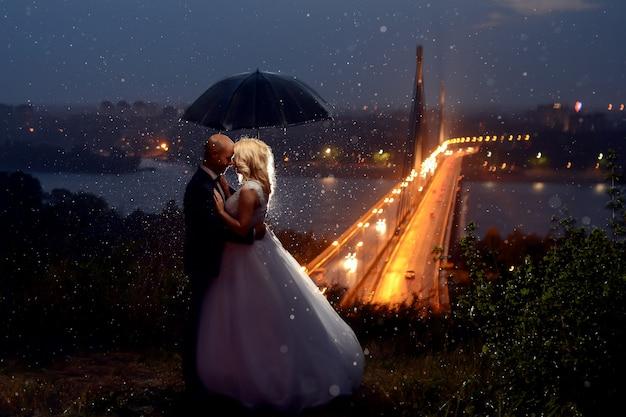 Recién casados bajo la lluvia besándose y cubriéndose con un paraguas