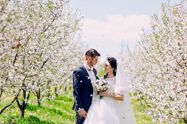 Recién casados mirándose con flores cayendo del cielo