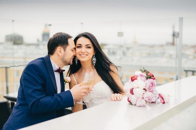Los recién casados románticos beben champán, tintinean vasos, están muy felices de celebrar su boda