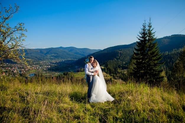 Los recién casados sonríen y se abrazan entre el prado en la cima de la montaña. paseo nupcial por el bosque en las montañas, las suaves emociones de la pareja