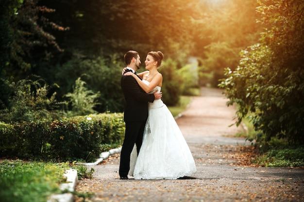 Recién casados sonrientes posando al atardecer