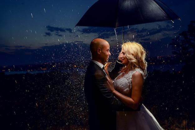 Recién casados sosteniendo un paraguas bajo la lluvia