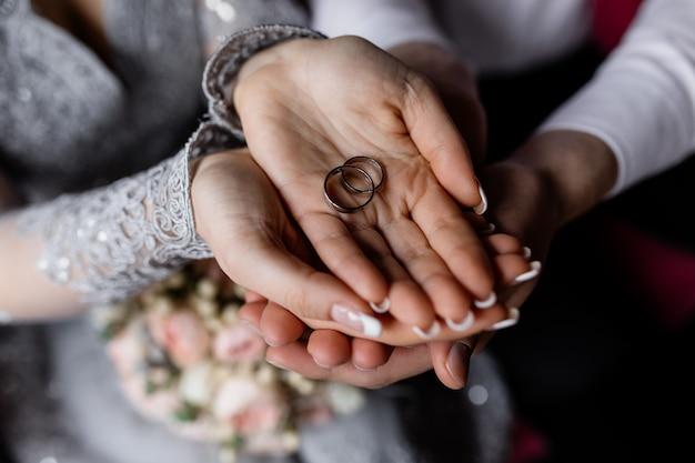 Los recién casados sostienen los anillos de boda en sus manos