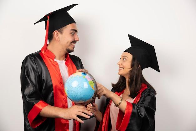 Recién graduados en bata mirando globo en blanco.