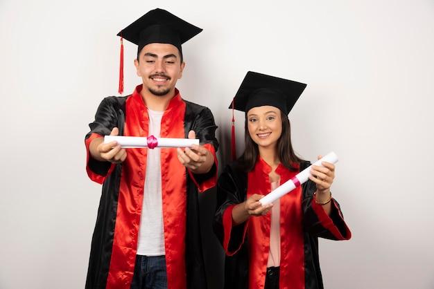 Recién graduados en bata mirando su diploma en blanco.