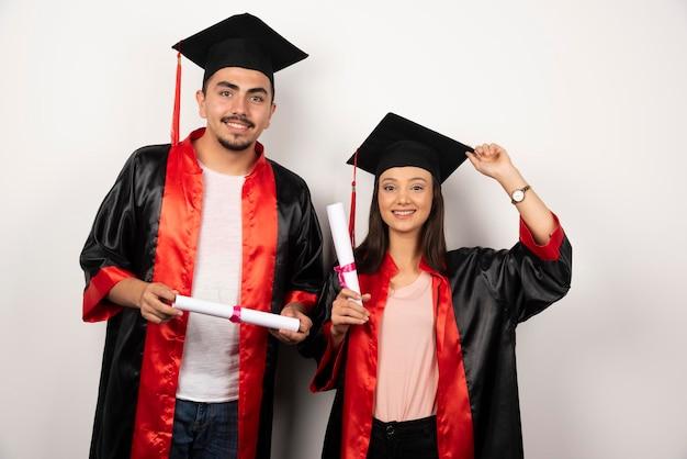 Recién graduados en bata posando con diploma en blanco.
