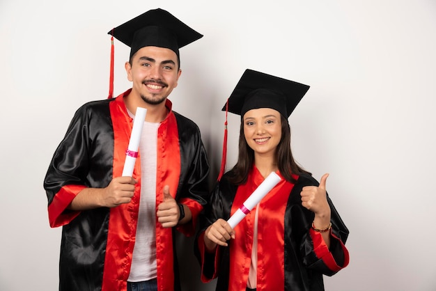 Recién graduados con diploma haciendo pulgares hacia arriba en blanco.
