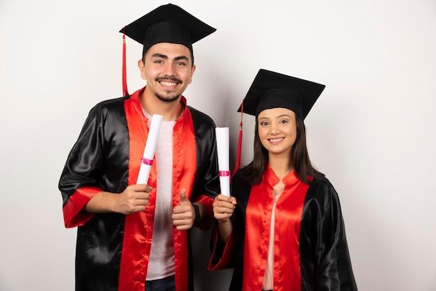 Recién graduados con diploma de pie en blanco.