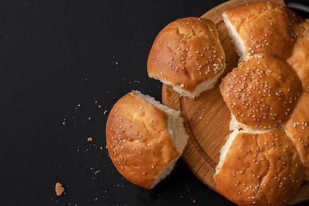 Recién horneado dulce dulce dividido bollo con semillas de sésamo en él, arrancado pedazo de pan