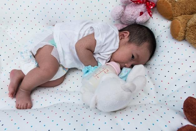 Recién nacido acostado en la cama y bebiendo leche de la botella, botella de enfoque