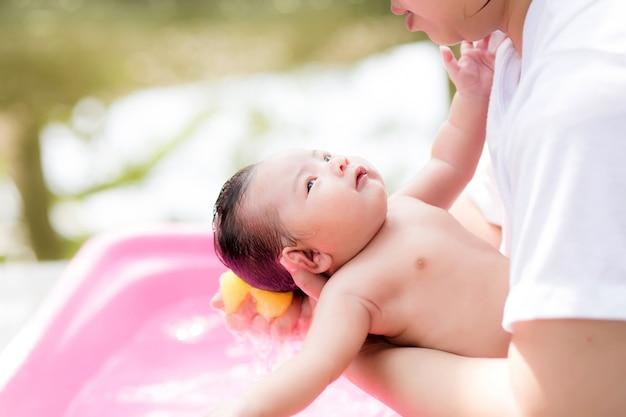 Recién nacido asiático tomando un baño en la cuenca de ping por nueva madre