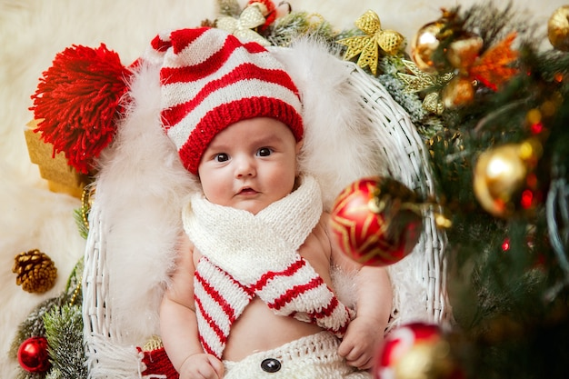 Un recién nacido debajo de un árbol de navidad